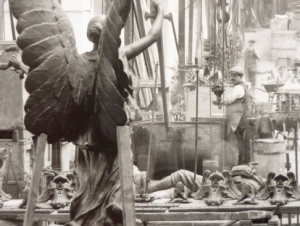 Detail from inside the foundry with Singers workers and the back view of the Shepherds Bush War memorial (still in situ today) by Henry Charles Fehr, a sculptor who had many of his works cast at Singers, including the dragon that graces the top of Cardiff's City Hall. Printed from the original glass plate negative