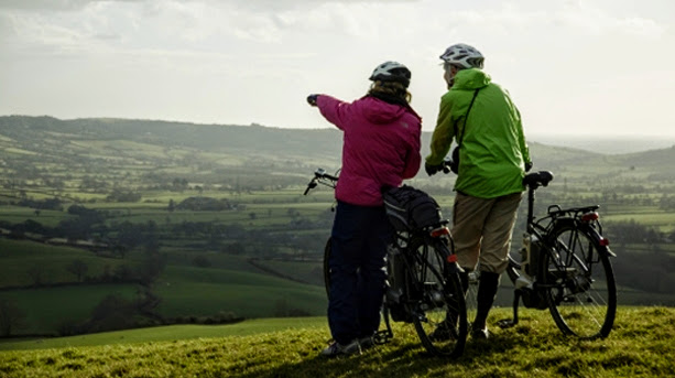Couple with bikes admiring a countryside view
