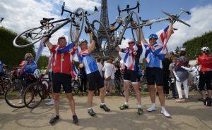 Cyclists lifting up their bikes in front of Eiffel tower at the end of London to Paris charity ride.