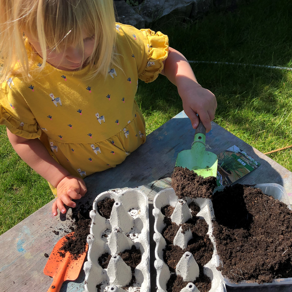 A young child scooping soil into an egg carton