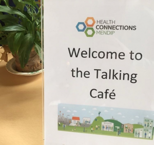 """Sign reading """"Welcome to the talking café"""""""