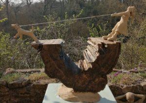 Wooden sculpture of dog pulling owner along
