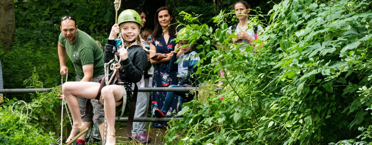 A child smiling while going down a zip wire