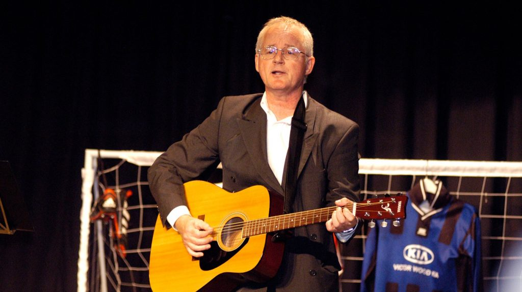 Graham Lloyd performing with guitar