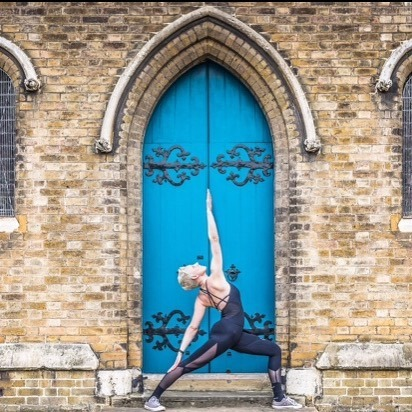 Lady in yoga pose in front of a blue door