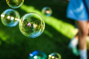 Soap bubbles floating above grass